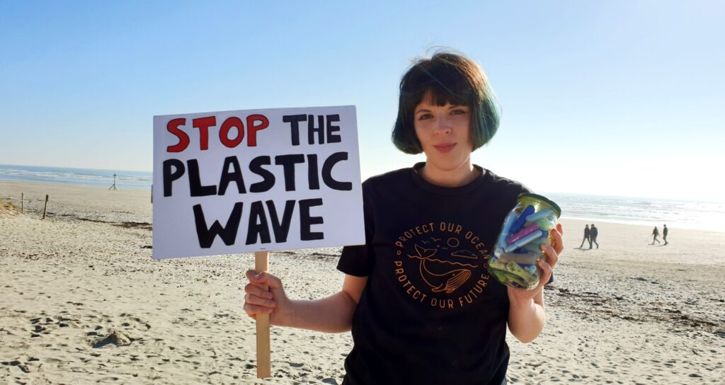 Ella Daish, with stop plastic waste sign on a beach